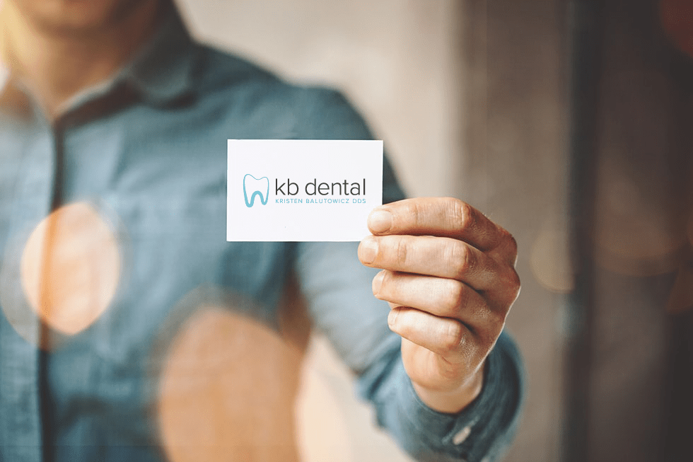 photo of a man holding a card to represent KB Dental's patient referral program